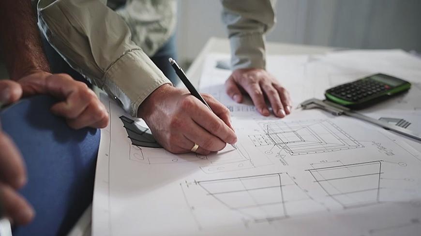 Image of engineer drawing schematics showing MCI's engineering capabilities.